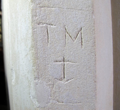 2. Framed initials T M, with anchor. South aisle pier.