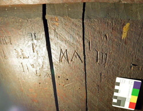 12. M or butterfly symbol and A (likely apotropaic), followed by I H.  Back of rood screen.
