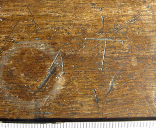 6. Letters A and T, probable initials. Middle aisle bench.