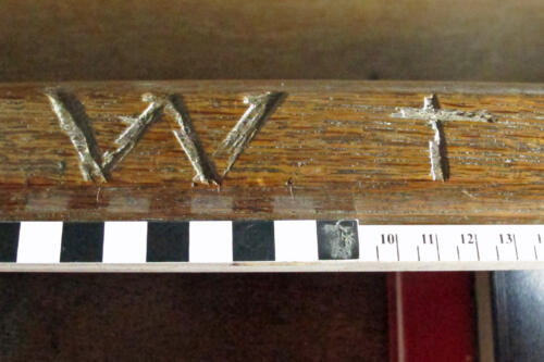10. Deeply carved W and cross on bench at back of north aisle. Initial of the seat occupant?