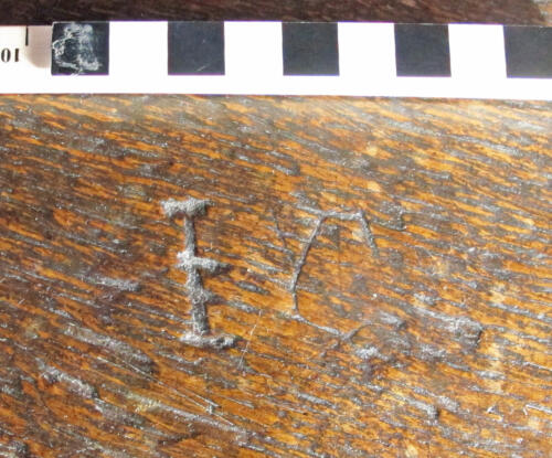 11. Nave bench. Crossed I  (or J), to which a C has been added.